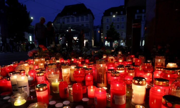 Flowers and candles in front of a closed and cordoned off department store in the city centre of Wuerzburg, Germany, on June 26, 2021. (Karl-Josef Hildenbrand/dpa via AP)