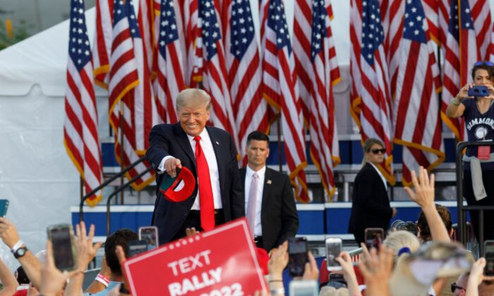 Former President Donald Trump points at individuals and throws hats into the crowd as he arrives for his campaign-style rally in Wellington, Ohio, on June 26, 2021. (Stephen Zenner/AFP via Getty Images)