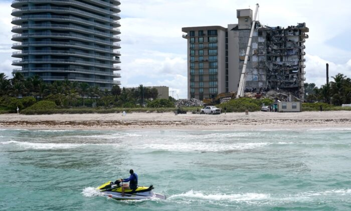 A jet ski rides by as rescue workers search in the rubble for survivors at the Champlain Towers South condominium, in the Surfside area of Miami, Fla., on June 26, 2021. (Lynne Sladky/AP Photo)
