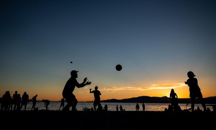 People are silhouetted while playing and gathering at English Bay Beach at sunset, in Vancouver, B.C., on June 21, 2021. A heat warning is in effect for most of Western Canada and the weather agency says numerous daily temperature records have been shattered across B.C. (The Canadian Press/Darryl Dyck )