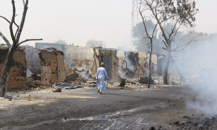 A man walks past shops burned down by suspected members of the Islamic State West Africa Province (ISWAP) during an attack, in the village of Auno, Nigeria, on Feb. 9, 2020. (Audu Marte/AFP via Getty Images)