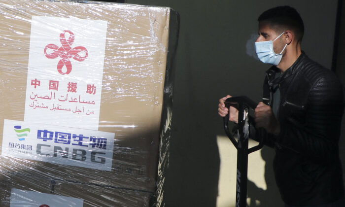 A Palestinian worker unloads a shipment of the Sinopharm COVID-19 vaccines donated by Beijing in the West Bank city of Nablus, on March 29, 2021. (Jaafar Ashtiyeh/AFP via Getty Images)