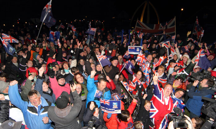 Islanders celebrate after the annouce of the referendum's result in Port Stanley, Falkland (Malvinas for Argentina) Islands, on March 11, 2013. Falkland Islanders were to vote  on the final day of a two-day referendum designed to make clear their staunch desire to remain British despite Argentina's sovereignty claims. Only three votes out of 1,517 were cast against the islands remaining British. (Tony Chater/AFP via Getty Images)