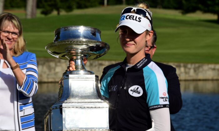 Nelly Korda holds the championship trophy as she celebrates winning the KPMG Women's PGA Championship golf tournament at the Atlanta Athletic Club in John's Creek, Ga., on June 27, 2021. (Adam Hagy/USA TODAY Sports)