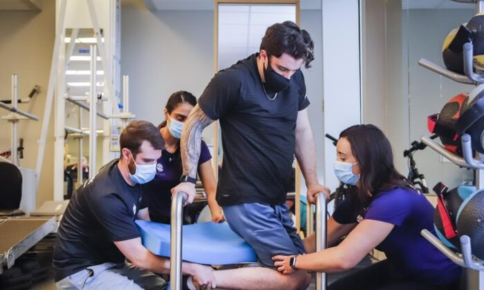 Humboldt Broncos bus crash survivor Ryan Straschnitzki, centre, is helped to turn his body by Eric Daigle, left, and Jill Mack while he attends a physiotherapy session in Calgary, Alta., June 24, 2021. (The Canadian Press/Jeff McIntosh)