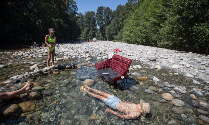 Albert Huynh cools off in the frigid Lynn Creek water as Leanne Opuyes, left, laughs in North Vancouver, B.C., on June 28, 2021. Environment Canada warns the torrid heat wave that has settled over much of Western Canada won't lift for days, although parts of British Columbia and Yukon could see some relief sooner. (The Canadian Press/Darryl Dyck)