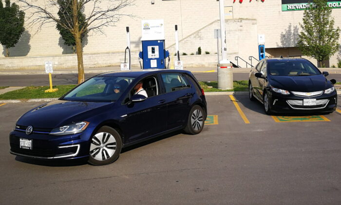 Electric vehicles are seen at a parking spot at Lansdowne Mall in Peterborough, Ontario, on June 17, 2018. The Parliamentary Budget Officer suggests that to make concerted progress toward the latest and most aggressive emissions reduction target, roughly half of new vehicle sales starting in 2022 should be zero-emission and be charged with zero-emission electricity. (The Canadian Press/Doug Ives)
