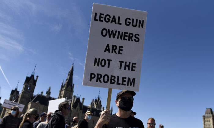 A gun owner holds  a sign as they participate in a rally organized by the Canadian Coalition for Firearm Rights against the government's new gun regulations, on Parliament Hill in Ottawa, on Sept. 12, 2020. (The Canadian Press/Justin Tang)