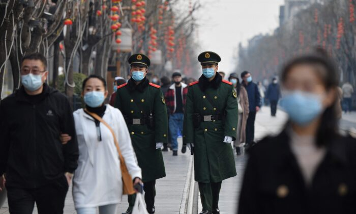 Two paramilitary police officers patrol in the area south of the Great Hall of the People during the second plenary session of the National People's Congress in Beijing on March 8, 2021. (Greg Baker/AFP via Getty Images)