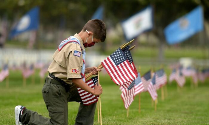A Boy Scout places miniature American flags at graves ahead of Memorial Day in the Los Angeles National Cemetery on May 29, 2021. (AGUSTIN PAULLIER/AFP via Getty Images)