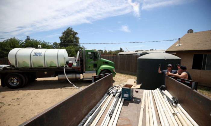 Chris McMillan with AEI Transportation, talks with Loren Scott Denney as she fills a tanks with potable water during the installation of a 2,500 gallon tank in front of his house after his well went dry on May 25, 2021, in Madera, California. Loren Scott Denney received a 2,500 gallon water tank from Central Valley nonprofit community development organization Self Help Enterprises after his well went dry. (Justin Sullivan/Getty Images)