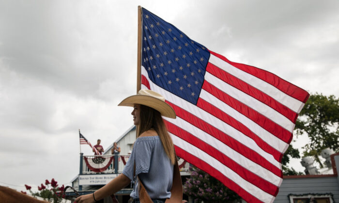 ROUND TOP, TX - JULY 04: Kaitlyn Tarnoswki, 14, carries an American flag while riding a horse during the 168th annual Round Top Fourth of July Parade on July 4, 2018 in Round Top, Texas. The Round Top community's Fourth of July celebration started in 1851 and is known as the longest running Fourth of July celebration west of the Mississippi. (Photo by Tamir Kalifa/Getty Images)