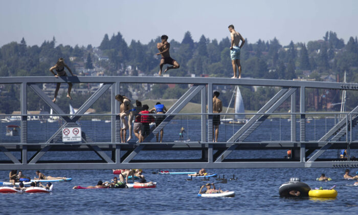 Two people jump from a pedestrian bridge at Lake Union Park into the water during a heat wave hitting the Pacific Northwest, on June 27, 2021. (John Froschauer/AP Photo)
