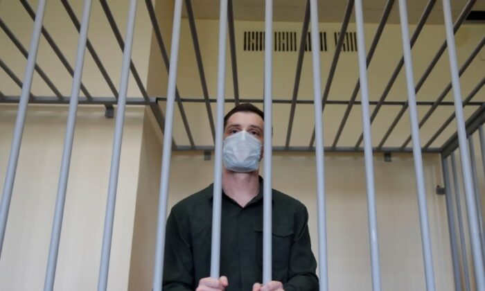 Former U.S. Marine Trevor Reed stands inside a defendants' cage during a court hearing in Moscow, Russia, on July 30, 2020. (Maxim Shemetov/Reuters)