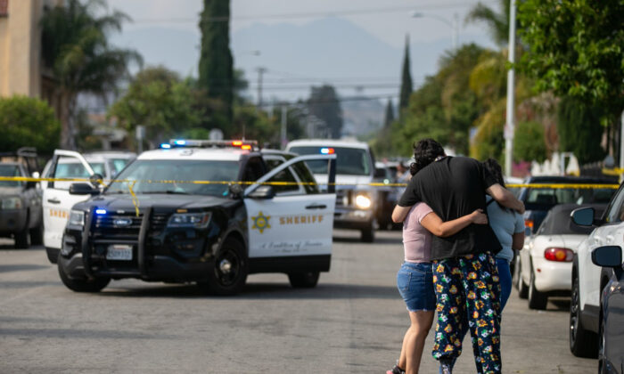 Neighbors embrace and the come to grips with three children being found dead at a home on South Ferris Ave in East Los Angeles, Calif., on June 28, 2021. (Jason Armond/Los Angeles Times/TNS)