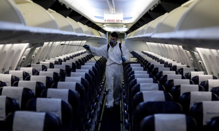 A worker in a protective suit disinfects a passenger plane of Smartwings airline at Vaclav Havel Airport in Prague, Czech Republic, on May 21, 2020. (David W Cerny/Reuters)