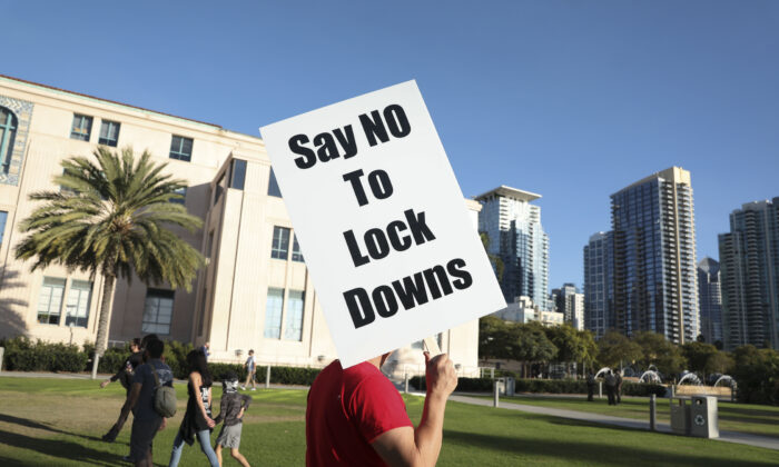 A man holds a sign opposing a lock-down during a rally at the County Administration Building, in San Diego, Calif., on Nov. 16, 2020. (Sandy Huffaker/Getty Images)