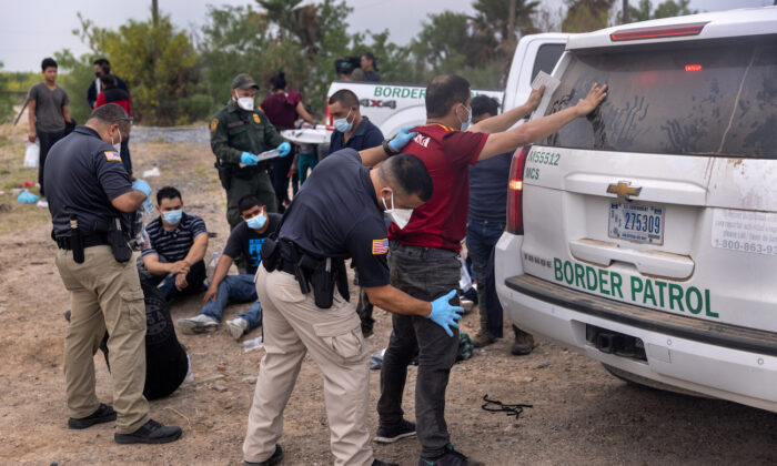 A transport officer searches immigrants before bussing them to a processing center after they crossed the border from Mexico in La Joya, Texas, on April 13, 2021. (John Moore/Getty Images)