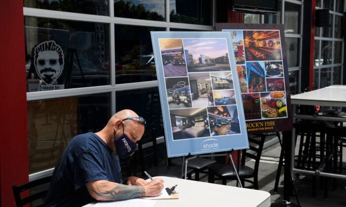 A man completes a job application before interviewing and later being hired on the spot for a job as a line cook during a job fair in Torrance, Calif., on June 23, 2021. (Patrick T. Fallon/AFP via Getty Images)