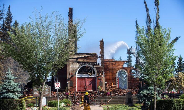 St. John Baptiste Parish Catholic church is shown in Morinville Alta, on June 30, 2021 as firefighters put out hot spots. A Catholic Church in northern Alberta has been destroyed by what RCMP are calling a suspicious fire. RCMP say in a release that officers were called to the blaze at St. John Baptiste Parish in Morinville, about 40 kilometres north of Edmonton, just after 3 a.m.. (The Canadian Press/Jason Franson)