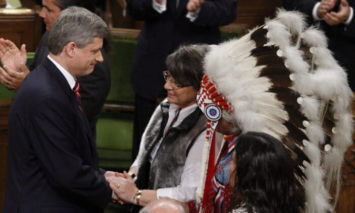 Inuit Tapiriit Kanatami President Mary Simon shakes hands with Prime Minister Stephen Harper, as Assembly of First Nations Chief Phil Fontaine watches, after the government's official apology for residential schools, in the House of Commons on June 11, 2008. (The Canadian Press/Fred Chartrand)