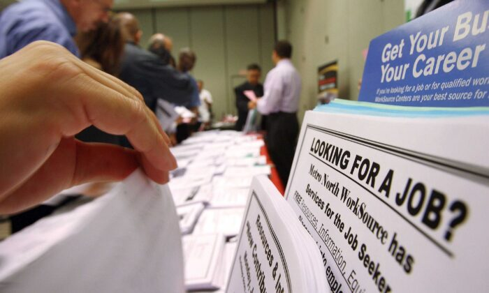 Job seekers look over job opening fliers at a WorkSource exhibit in this file photo. (David McNew/Getty Images)