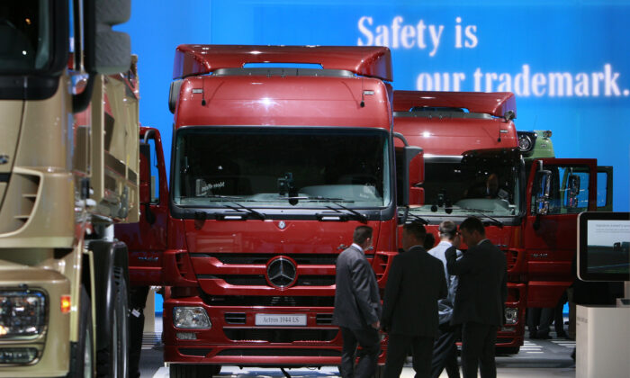 Visitors stand in front of a display of heavy trucks at the entrance to the Daimler exhibition area during a preview day at the IAA commercial vehicles trade fair in Hanover, Germany, on Sept. 24, 2008. (Christian Charisius/Files/Reuters)