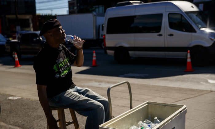 Carl Goodwin, manager of Seattle Sausage, takes a water break while selling bottles of water to baseball fans leaving the Mariners game on June 23, 2021. (Amanda Snyder/The Seattle Times/TNS)