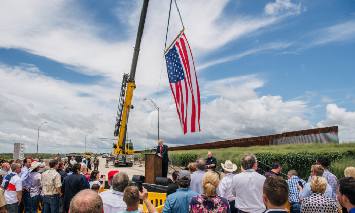 People listen to former President Donald Trump's address during a tour to an unfinished section of the border wall in Pharr, Texas, on June 30, 2021. (Brandon Bell/Getty Images)