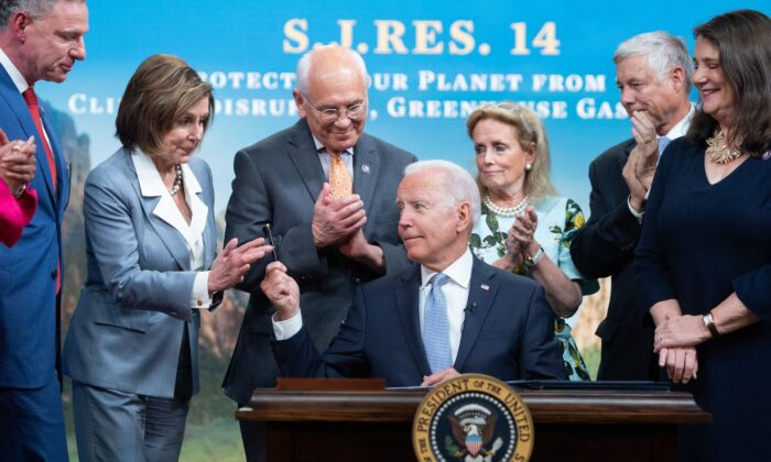 President Joe Biden hands a pen to House Nancy Pelosi (2nd L), alongside other members of the House, after signing a bill dealing with greenhouse gas emissions, in the Eisenhower Executive Office Building, in Washington, on June 30, 2021. (Saul Loeb/AFP/Getty Images)