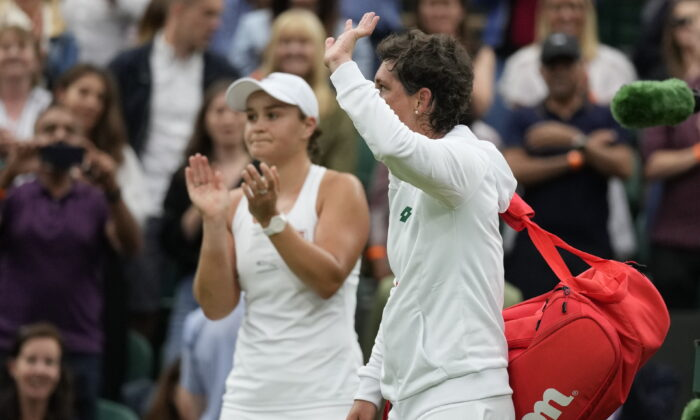 Spain's Carla Suarez Navarro leaves the court after being defeated by Australia's Ashleigh Barty (L) in the women's singles first round match against on day two of the Wimbledon Tennis Championships in London, on June 29, 2021.(Kirsty Wigglesworth/AP Photo)
