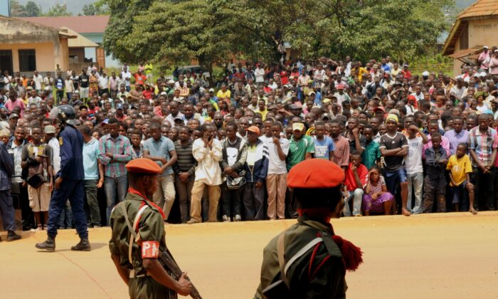 Servicemen of the Armed Forces of the Democratic Republic of Congo stand guard as people gathered to attend the public hearing of suspected members of the Allied Democratic Forces, a terrorist group, in Beni on Aug. 20, 2016. (Kudra Maliro/AFP via Getty Images)