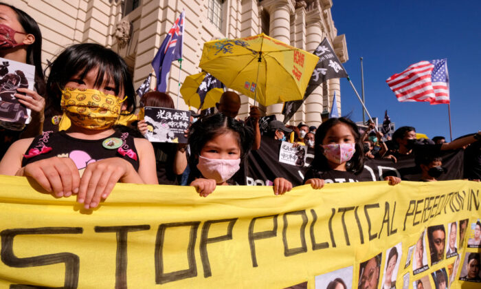 """Young participants hold a banner during a """"Stand With Hong Kong"""" rally in Pasadena, Calif., on June 12, 2021. (Ringo Chiu/AFP via Getty Images)"""