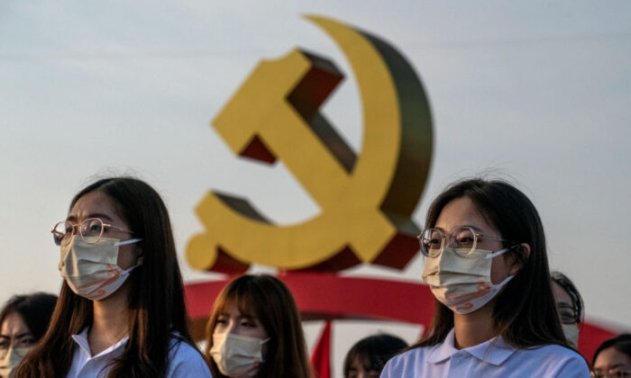 Chinese women stand in front of a large Communist Party logo at a ceremony marking the 100th anniversary of the Communist Party at Tiananmen Square in Beijing, China, on July 1, 2021. (Kevin Frayer/Getty Images)