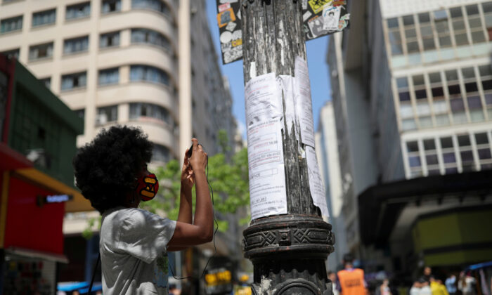 A woman photographs with her phone a job opportunity on job listings posted on a light pole in downtown Sao Paulo, Brazil, on Sept. 30, 2020. (Amanda Perobelli/Reuters)