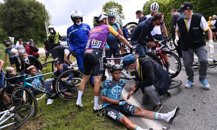 KTM rider Cyril Lemoine of France receives medical attention in Tour de France, between Brest and Landerneau, France, on June 26, 2021. (Anne-Christine Poujoulat/Pool via Reuters)
