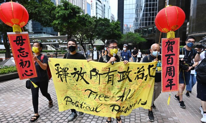 Four members of Hong Kong League of Social Democrats are marching on streets to urge the Beijing regime to release all political prisoners in Hong Kong on July 1, 2021. (Song Bilong/The Epoch Times)
