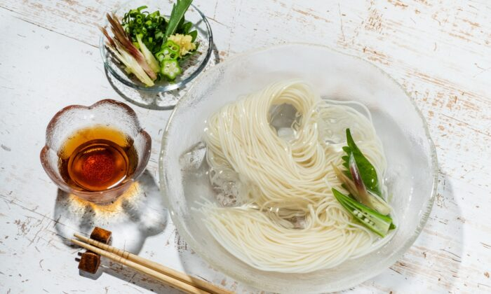Bundles of chilled somen are typically served on a family-style platter, with individual bowls of tsuyu for dipping and a variety of accoutrements for topping. (norikko/Shutterstock)
