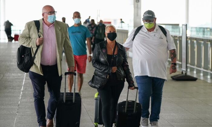 Charlotte Charles (center) and Tim Dunn (right), the parents of Harry Dunn, with Family advisor Radd Seiger (left), arrive at Terminal 2 of Heathrow Airport, London, on June 29, 2021. (Andrew Matthews/PA)