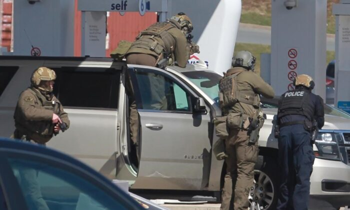 RCMP officers prepare to take a person into custody at a gas station in Enfield, N.S., on April 19, 2020. The RCMP in Nova Scotia have called in the Ontario Provincial Police to investigate the unauthorized release of 911 calls recorded the night a lone gunman started a killing rampage that led to the deaths of 22 people. (The Canadaian Press/Tim Krochak)