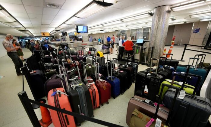 Baggage stacks up from delayed travellers in the baggage claim area in Denver International Airport on June 16, 2021, in Denver. (AP Photo/David Zalubowski)