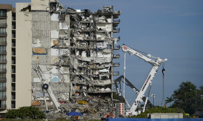 Workers peer up at the rubble pile at the partially collapsed AP Photo Champlain Towers South condo building in Surfside, Fla., on July 1, 2021. (Mark Humphrey/AP Photo)