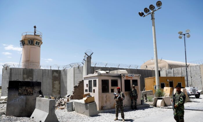 Afghan soldiers stand guard at the gate of Bagram U.S. air base, on the day the last of American troops vacated it, in Parwan province, Afghanistan on July 2, 2021. (Mohammad Ismail/Reuters)