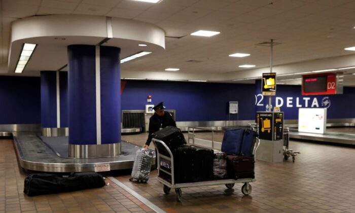 A baggage claim employee grabs bags from an empty baggage claim area in Delta terminal at LaGuardia Airport in New York, on March 21, 2018. (Shannon Stapleton/Reuters)