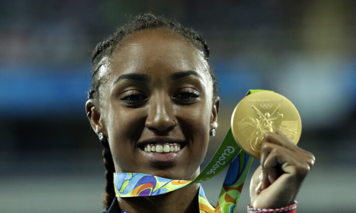 Gold medal winner Brianna Rollins from the United States shows off her medal during the medal ceremony for the women's 100-meter hurdles final, at the Olympic stadium in Rio de Janeiro, Brazil. Thursday, Aug. 18, 2016. (Dmitri Lovetsky/AP Photo)