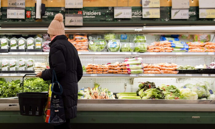 A woman looks over produce in a grocery store in Toronto on Nov. 30, 2018. (The Canadian Press/Nathan Denette)