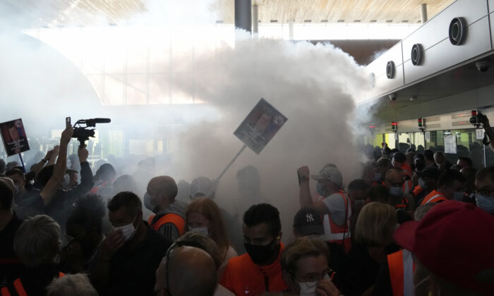 Smoke rises from a flare during scuffles between protesters and French police in front of the passport control of Terminal 2E of Charles de Gaulle Airport in Paris on July 2, 2021. (Thanassis Stavrakis/AP Photo)