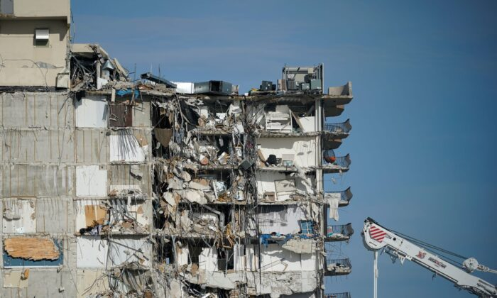 A parked crane sits beside the still standing section of Champlain Towers South, which partially collapsed last Thursday, as rescue efforts on the rubble below were paused out of concern about the stability of the remaining structure in Surfside, Fla., on July 1, 2021. (Mark Humphrey/AP Photo)