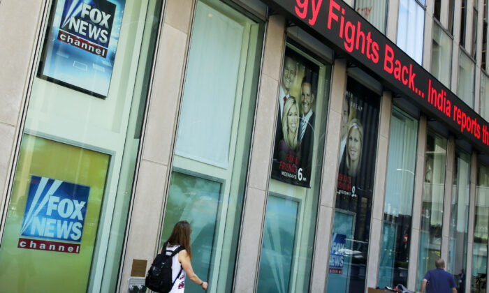 People pass the News Corporation headquarters building and Fox News studios in New York City on Aug. 1, 2017. (Richard Drew/AP Photo)