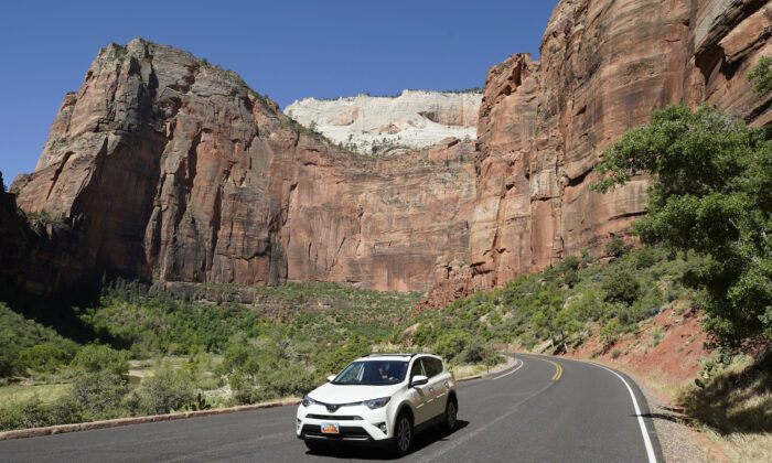 A lone car makes its way down a road in Zion National Park in Springdale, Utah, on May 15, 2020. (George Frey/Getty Images)